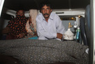 Mohammad Iqbal, right, husband of Farzana Parveen, sits in an ambulance next to the body of his pregnant wife. Photo / AP