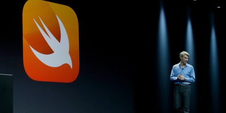 Apple senior vice president of Software Engineering Craig Federighi walks next to a symbol for Swift, a new programming language. Photo / AP