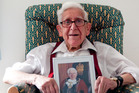 Bernard Jordan an 89-year-old veteran, holding a picture of himself as the Mayor of Hove. Photo / AP