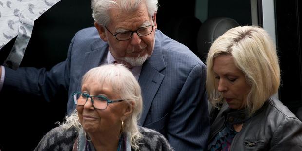 Veteran Australian-British entertainer Rolf Harris, center, his wife Alwen Hughes, bottom, and his daughter Bindi, right, arriving at court. Photo / AP