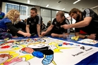 Alana Blow gets Dane Coles, Tony Woodcock and Sam Whitelock involved with some colouring-in yesterday. Photo/ Brett Phibbs