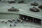 Bicycle commuters pass through a tunnel while, above, tanks are positioned in Beijing, two days after the Tiananmen Square killings. Photo / AP