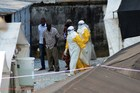 Health workers wearing protective suits walking in an isolation center for people infected with Ebola. Photo / AFP