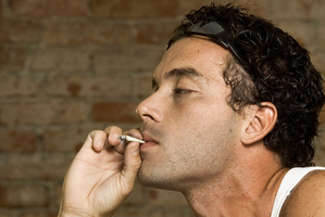 Side profile of a man smoking a joint