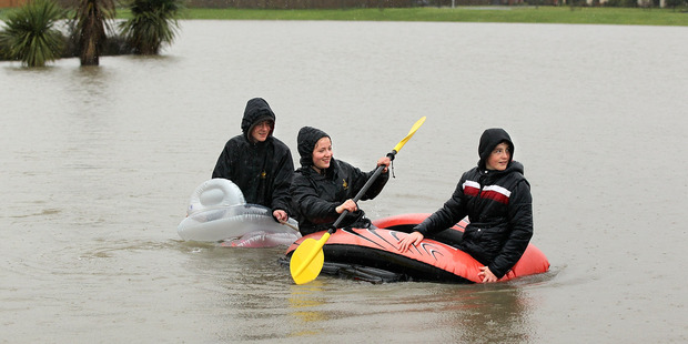 Hamish McEwan, 15, Rose McEwan, 16, and James McEwan, 12 paddle their inflatable lilos on a flooded play ground in Rangiora. Photo / Getty Images