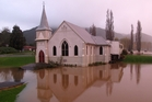 Kaeo's Union Church reflected in floodwater at dusk on Tuesday. Photo/Peter de Graaf