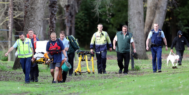 Emergency services assist a woman trapped in mud at Kowhai Park this morning. Wanganui Chronicle photo by Stuart Munro