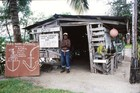 An 80-year-old Ni-Vanuatuan stands proudly outside his museum of WWII military artefacts.