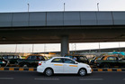 An Uber taxi drives past traditional black-and-yellow licensed cabs in New Delhi, India. Uber is now in 128 cities and approximately 40 countries. Photo / AP