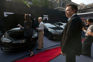 Tesla Motors CEO Elon Musk, right, looks on as a set of Tesla Model S sedans are delivered to its first customers in China at an event in Beijing.