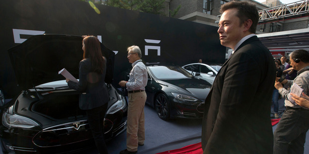 Tesla Motors CEO Elon Musk, right, looks on as a set of Tesla Model S sedans are delivered to its first Chinese customers at an event in Beijing earlier this year. Musk announced today that many of the Telsa patents will be open to rivals. Photo / AP