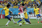 Brazil's Marcelo, left, tries to clear the ball but scores on his own goal during the group A World Cup soccer match between Brazil and Croatia. Photo / AP