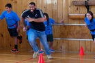 Charlie Faumuina takes part in a game at Melville Intermediate School, Hamilton, yesterday during a promotional visit with other All Blacks. Photo / Alan Gibson