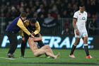 A streaker is arrested after running onto the field as Luther Burrell of England looks on. Photo / Martin Hunter / Getty Images