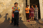 Palestinian children stand near their house eating corn at the Shati refugee camp, in Gaza City. Photo / AP