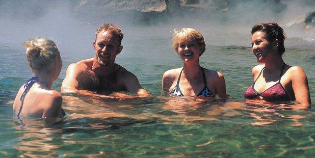 Taking the waters at Hot Water Beach, Lake Tarawera. Photo / Destination Rotorua