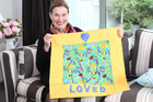 Loved 4 Life founder Marcia Guest-McGrath with one of the organisation's signature handcrafted bassinet quilts. Photo / Cloe Willetts