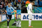 Uruguay's Luis Suarez celebrates the matchwinner while Wayne Rooney reacts to the 2-1 defeat. Photo / AP