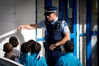 A police officer talks to children after the stabbing at the Pacific Christian School in Mangere Bridge yesterday. Photo / Sarah Ivey