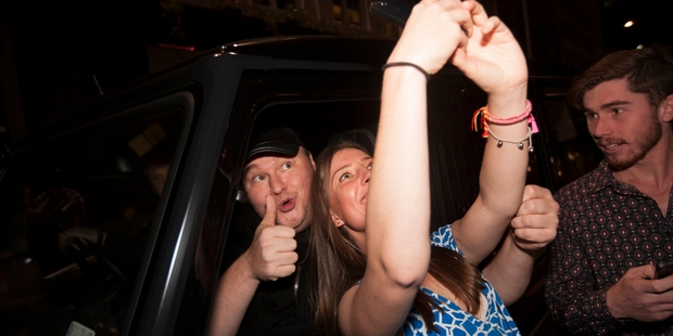 A woman takes a selfie with Dotcom before he heads to his mansion. Photo / Chris Loufte