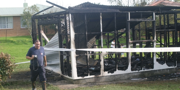 Craig Bain examines the remains of the garage destroyed by fire on Sunday morning. Photo/Peter Jackson