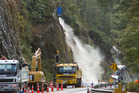 Workers flush out slip risks on State Highway 36 using thousands of litres of water dropped from a helicopter monsoon bucket. Photo / Ben Fraser