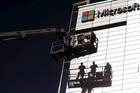 Workers install the Microsoft logo on the wall of Nokia's former headquarters in Espoo, Finland. Microsoft has decided to use the Android operating system in its new Nokia smartphone. Photo / AP