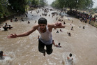 A boy jumps as people cool themselves off in a canal in Lahore, Pakistan. Photo / AP