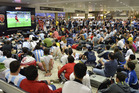 Hundreds of travelers watch the World Cup match between Germany and Ghana on a screen in the departure lobby at the airport in Belo Horizonte, Brazil. Photo / AP