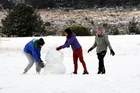 Tourists enjoy the snow on the lawn of the Chateau Tongariro at National Park. Photo / SNPA