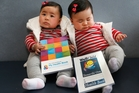 Ella Gao (left) shows off the new health book which replaces the one her twin sister, Grace, has. Photo / Mark Mitchell