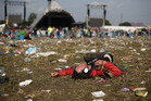A festival goer rests among litter strewn across the field near to the main Pyramid Stage of the Glastonbury Festival. Photo/AP