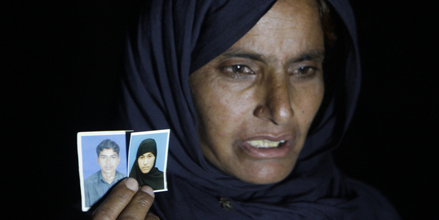 A Pakistani woman Nargas Bibi shows family pictures of her son Sajjad Ahmed and his wife Muafia Bibi, who were killed by Bibi's parents. Photo / AP