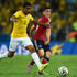 Paulinho of Brazil and Colombia's James Rodriguez tussle for the ball in the opening stages of the match.