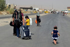 An Iraqi family leave their hometown Mosul, walking towards Irbil. Photo / AP