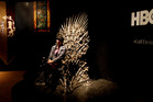 A woman sits on a replica of the throne which is part of the Game of Thrones exhibition. Photo / AP