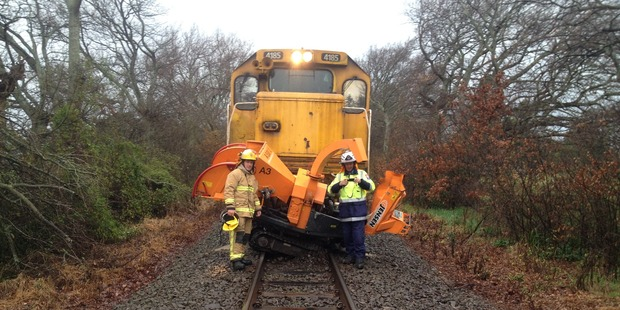 Firemen beside the remains of a wood chipper, struck by a goods train near Lincoln Rd, Carterton.