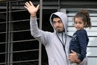 Luis Suarez, with his daughter  in Montevideo after returning from the World Cup, has apologised for his ill-judged bite. Photo / AP