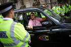 A London taxi driver talks to police during a protest against Uber. Photo / Getty Images