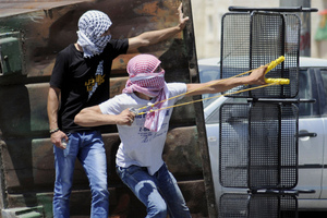 A Palestinian uses a sling shot during clashes with Israeli border police in Jerusalem. Photo / AP