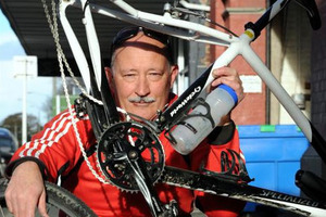 Cyclist Pascal Sutherland holds his bike, which was damaged when a motorist ran over it on Saturday. Photo / Craig Baxter / Otago Daily Times
