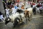 Participants run behind Torrestrella's bulls during the first bull-run of the San Fermin Festival. Photo / AFP