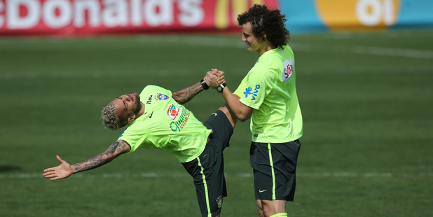Brazil's Daniel Alves, left, stretches with David Luiz during a practice session at the Granja Comary training center, in Teresopolis, Brazil. Photo / AP