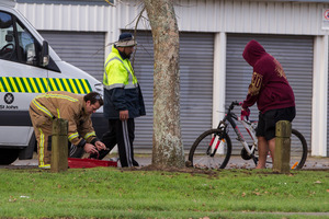 Emergency services help after a young girl impaled herself on the handle bar of a bicycle. Photo / Michael Craig
