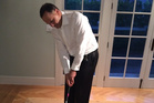 John Key tries out his presidential putter which carries the United States presidential seal and Barack Obama's signature.