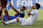 Uruguay's Luis Suarez holds his teeth after biting Italy's Giorgio Chiellini's shoulder. Photo / AP