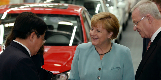 German Chancellor Angela Merkel, chats with FAW Group President Xu Jianyi, left, and Volkswagen CEO Martin Winterkorn, right, as they visit the FAW-Volkswagen production plant in Chengdu. Photo / AP