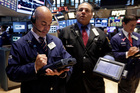 Fred DeMarco, left, works with fellow traders on the floor of the New York Stock Exchange. File photo / AP