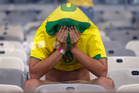 A Brazil fan covers his face after the World Cup semifinal soccer match between Brazil and Germany at the Mineirao Stadium in Belo Horizonte. Photo / AP