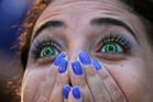 A Brazil soccer fan wearing contact lenses that mimic the Brazilian flag reacts as she watches her team play Germany in a World Cup semifinal game. Photo / AP